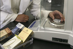 Tobaco is weighed using a scale.